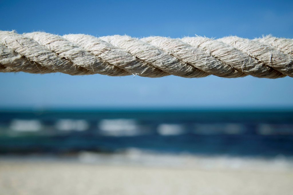 Stock Photo: 1747R-18349 Close_up of weathered rope with beach in background