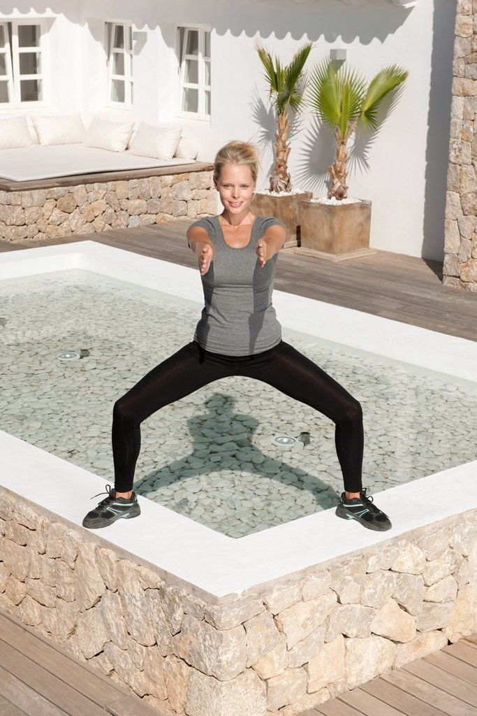 Stock Photo: 1747R-18353 Young woman exercising in patio