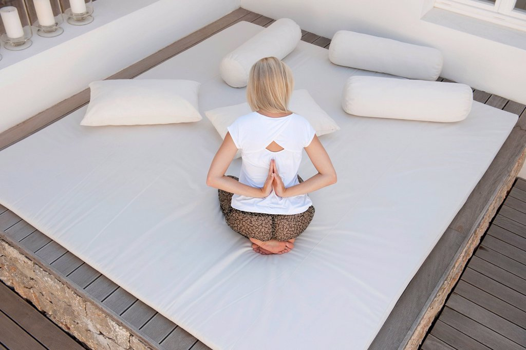 Stock Photo: 1747R-18359 Woman doing reverse prayer pose on bed in patio, rear view