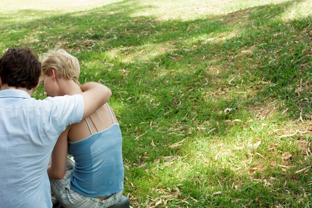 Stock Photo: 1747R-18360 Couple sitting together on grass, rear view