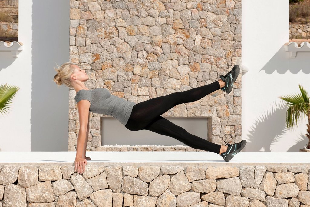 Young woman doing pilates exercise outdoors, eyes closed, side view : Stock Photo