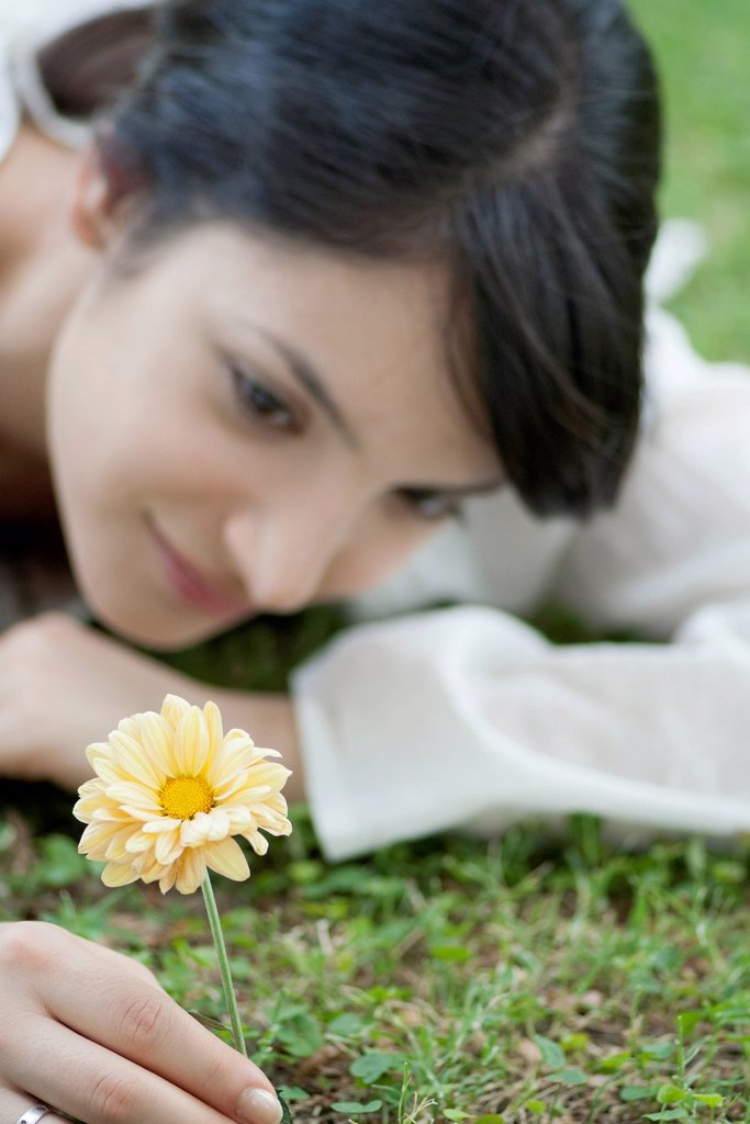 Young woman lying on grass looking at yellow flower : Stock Photo