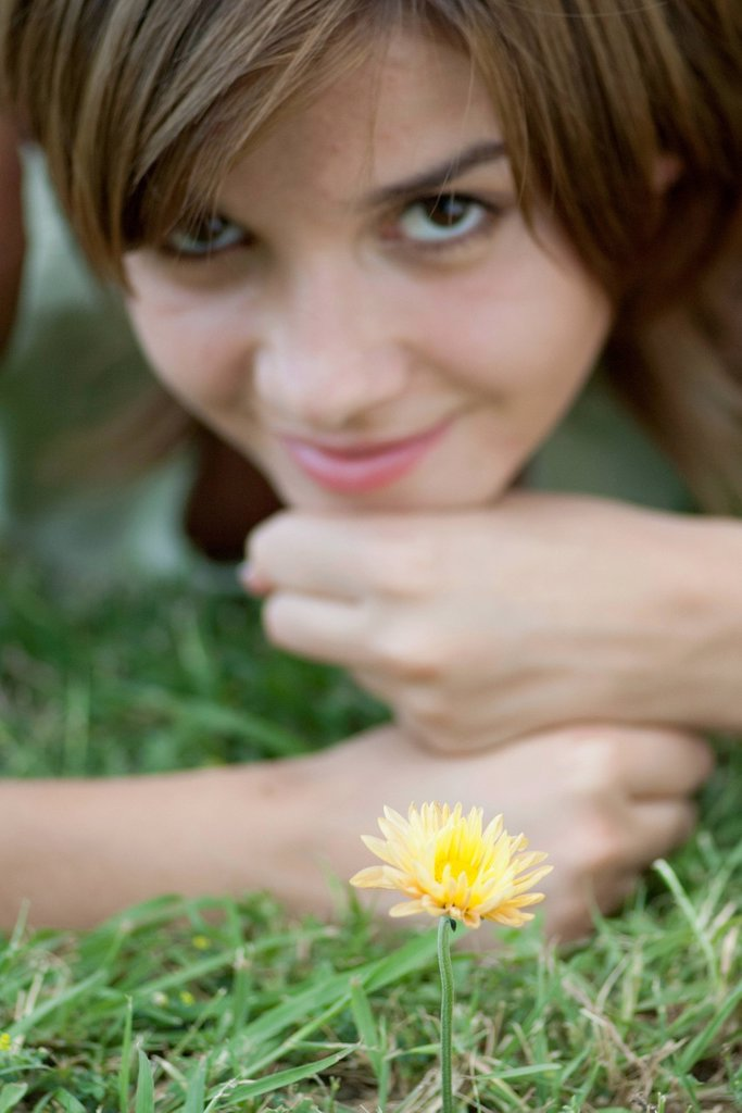 Stock Photo: 1747R-18385 Young woman lying in grass by yelllolw flower