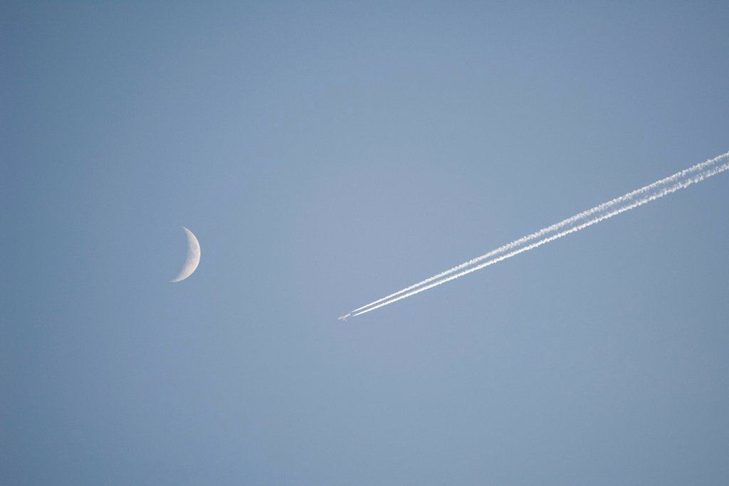 Stock Photo: 1747R-18393 Vapor trail and crescent moon in sky