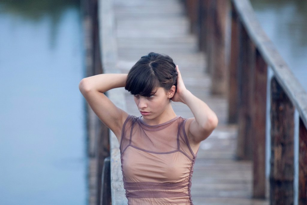 Stock Photo: 1747R-18401 Young woman walking on dock with hands in hair