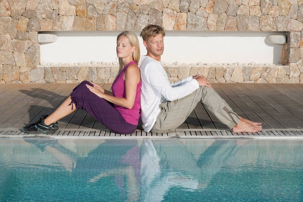 Young couple sitting back to back at poolside : Stock Photo
