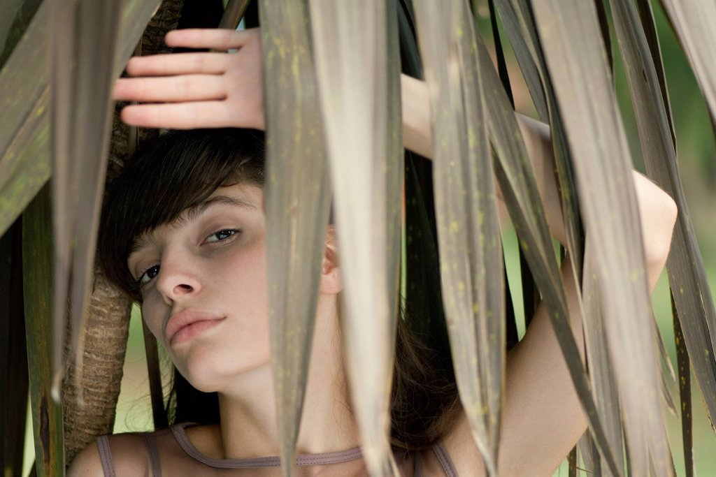 Stock Photo: 1747R-18411 Young woman behind tropical foliage, portrait