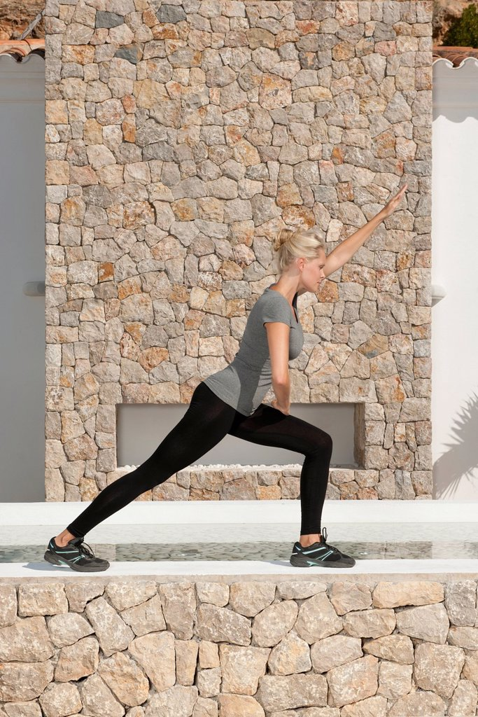 Young woman stretching legs outdoors : Stock Photo