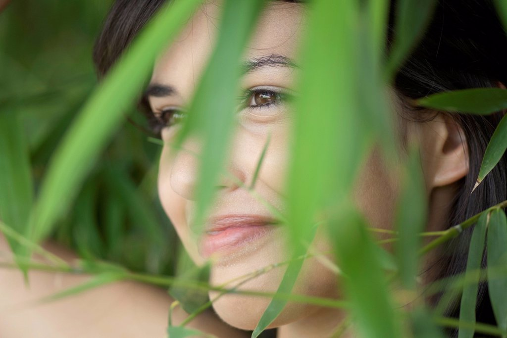 Young woman behind foliage, portrait : Stock Photo