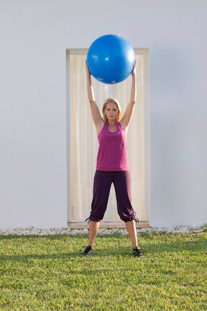 Stock Photo: 1747R-18424 Young woman holding up fitness ball above head