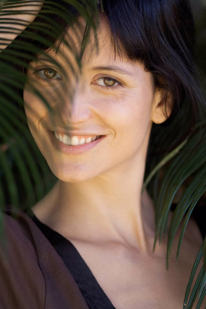Stock Photo: 1747R-18442 Young woman looking through palm leaf, smiling, portrait