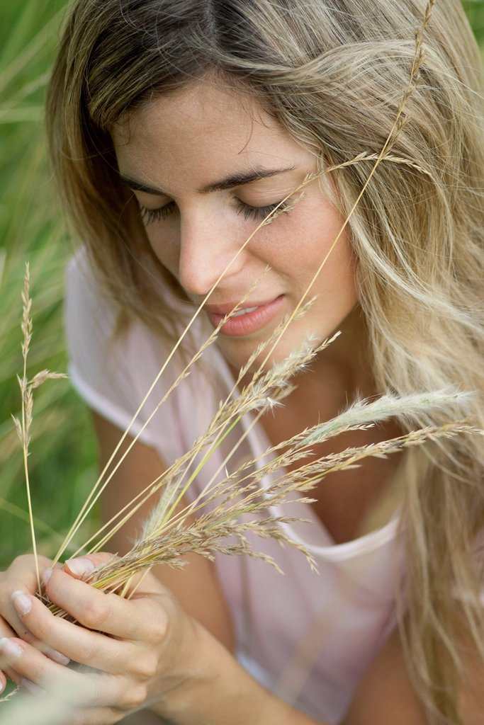 Stock Photo: 1747R-18447 Young woman holding grass with eyes closed