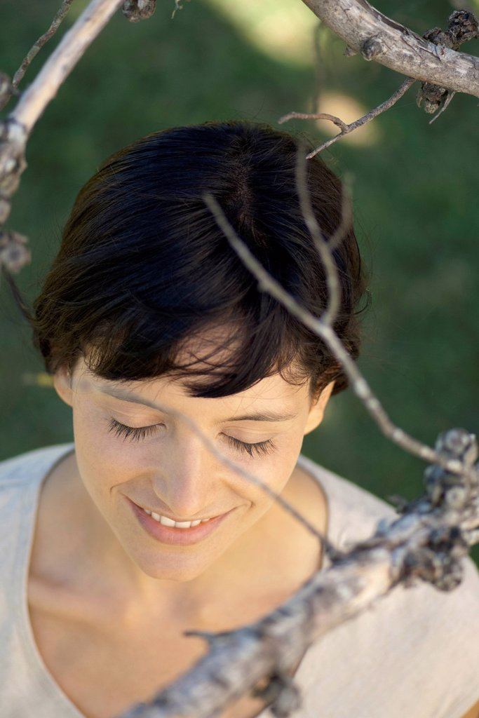 Woman under tree branches with eyes closed, smiling : Stock Photo