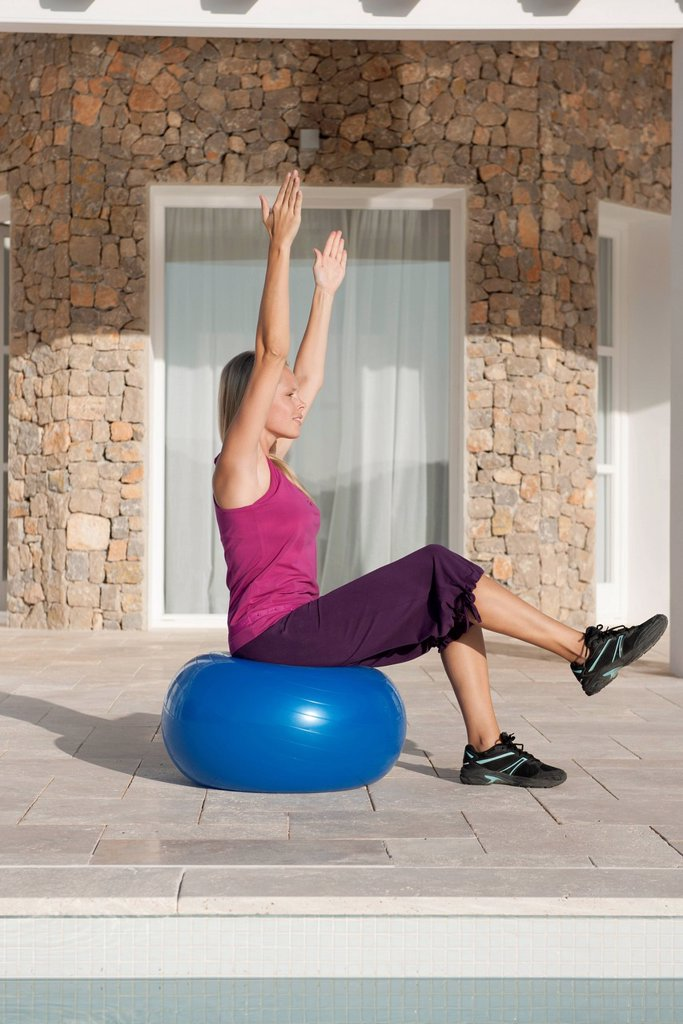 Young woman doing exercise on fitness ball : Stock Photo