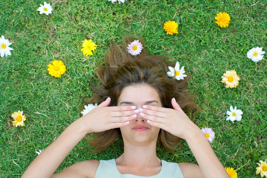 Stock Photo: 1747R-18464 Woman lying on grass surrounded by flowers with hands covering eyes