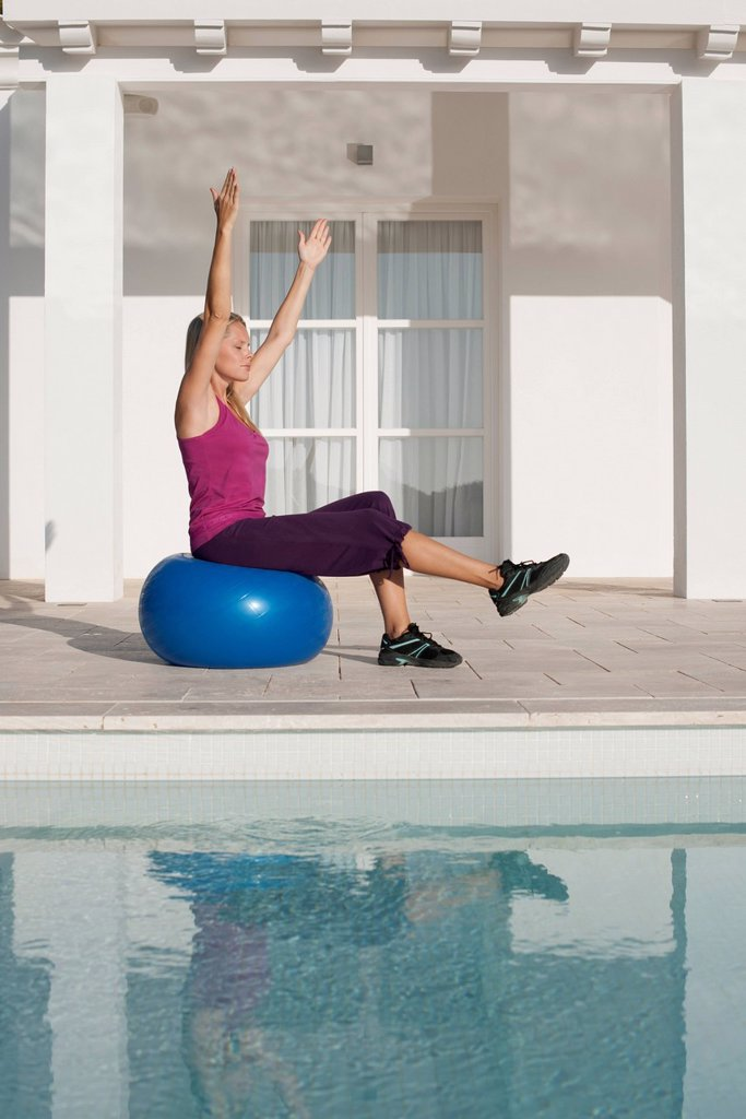 Young woman doing exercise on fitness ball at poolside : Stock Photo