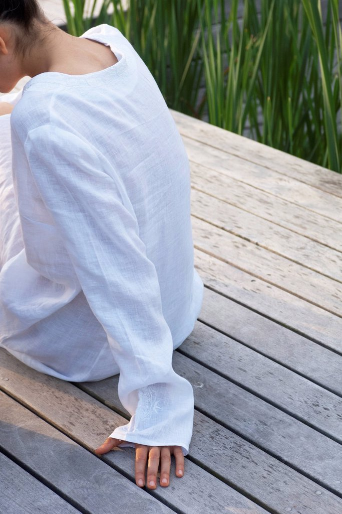 Woman sitting on wooden deck, cropped rear view : Stock Photo