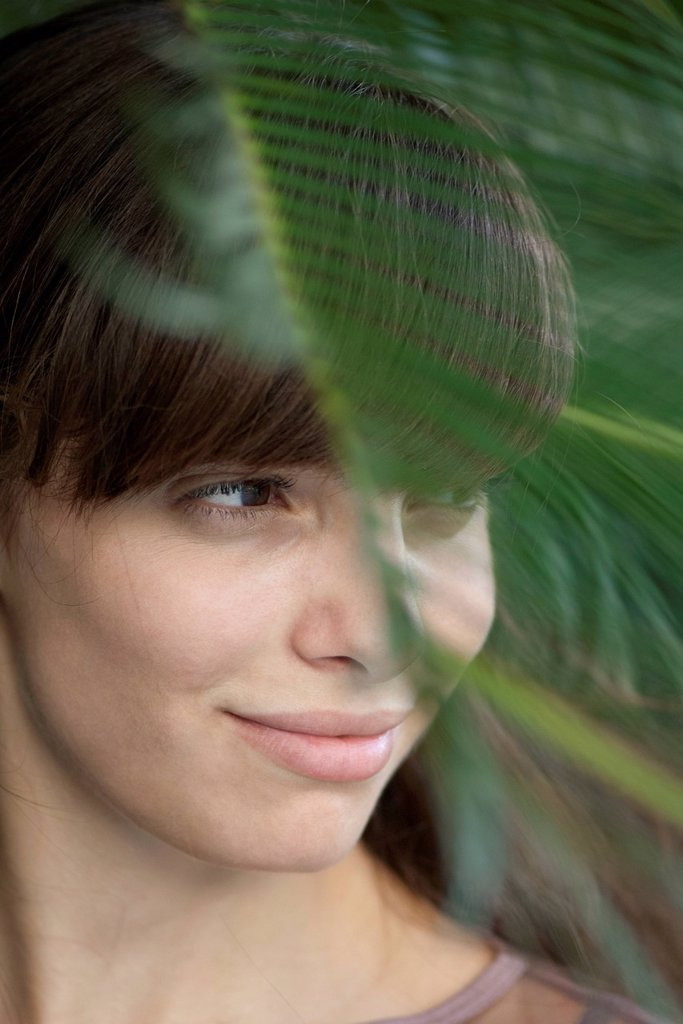 Young woman behind palm frond, looking away in thought : Stock Photo