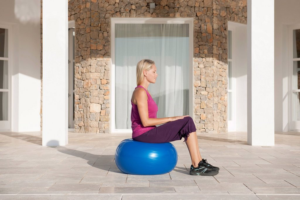 Young woman sitting on fitness ball with eyes closed : Stock Photo