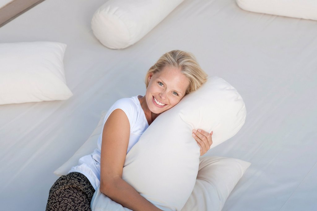 Stock Photo: 1747R-18517 Young woman hugging pillow on bed