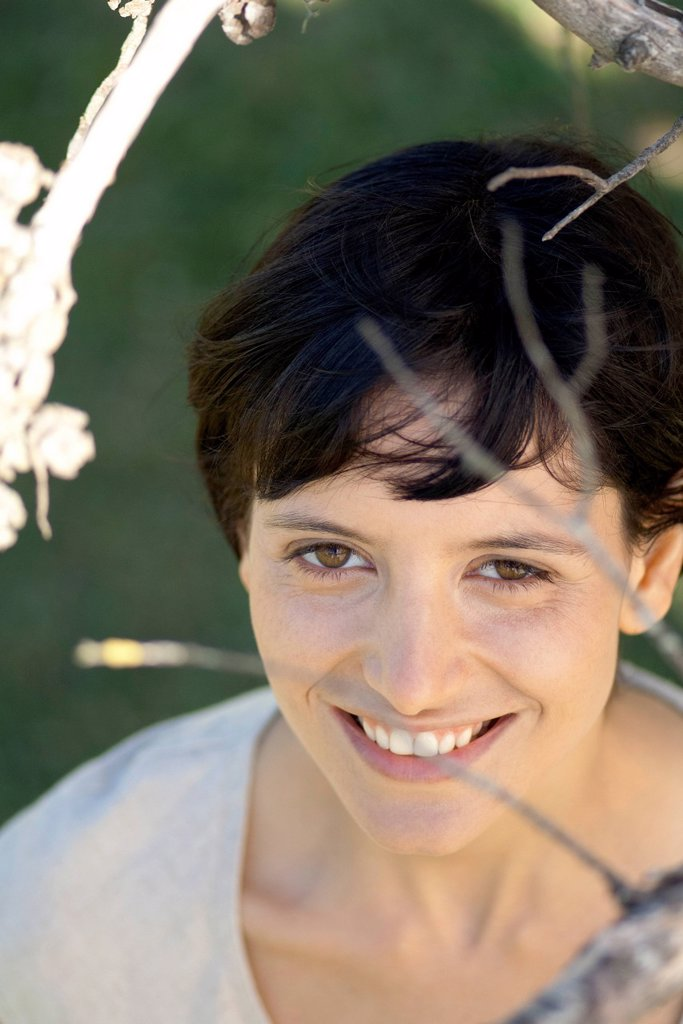 Young woman smiling through tree branches, portrait : Stock Photo
