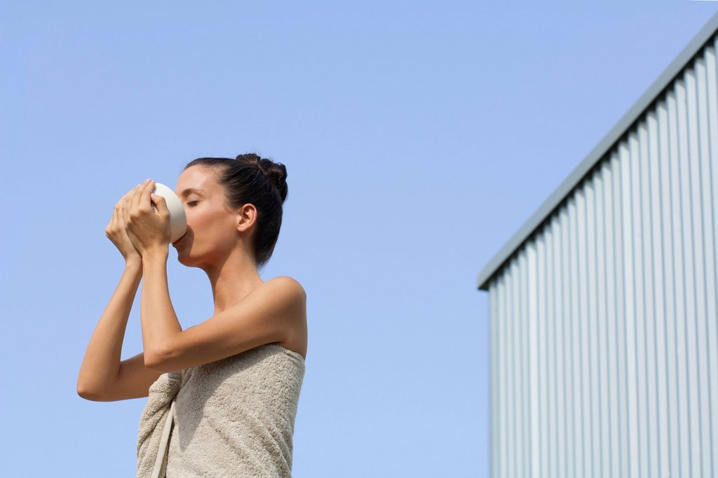 Mid_adult woman wrapped in towel drinking from bowl, side view : Stock Photo