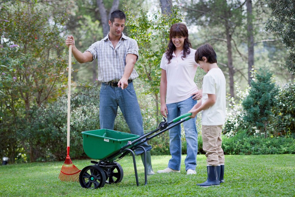 Stock Photo: 1747R-18537 Father and two children working together in yard