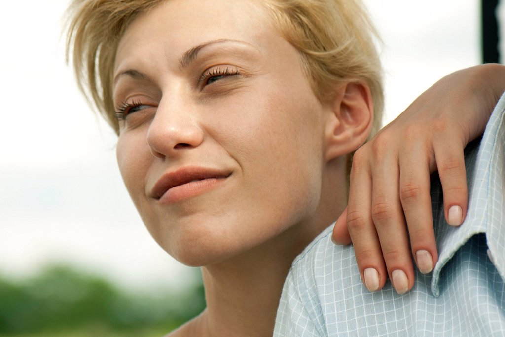 Young woman with hand on man´s shoulder, looking away and smiling : Stock Photo