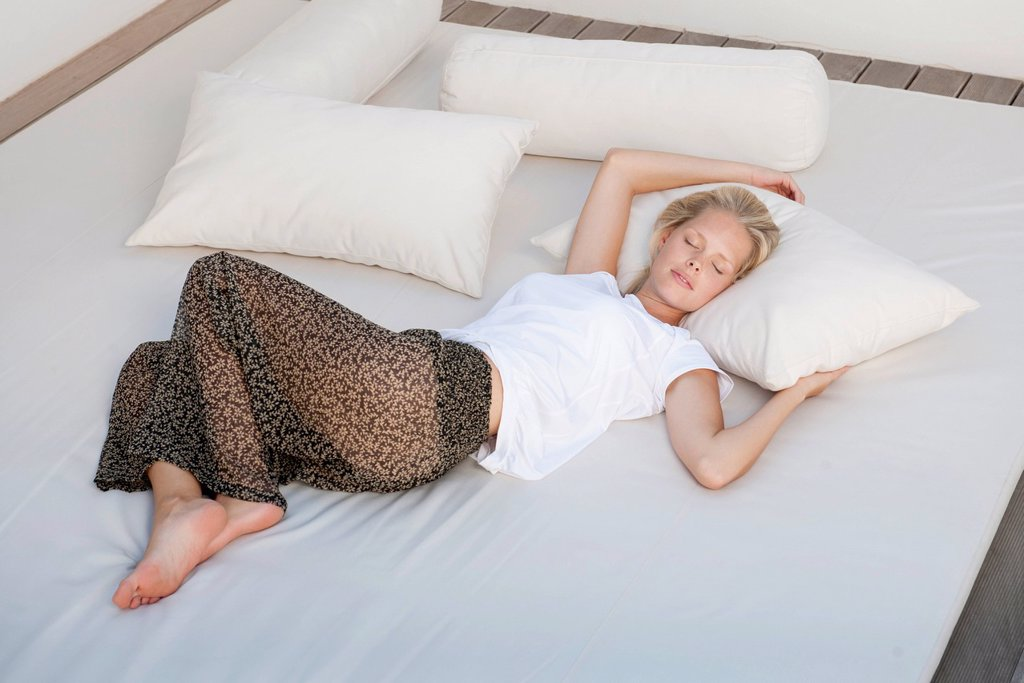 Stock Photo: 1747R-18551 Young woman sleeping on bed