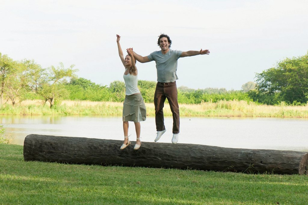 Young couple jumping off log in park : Stock Photo
