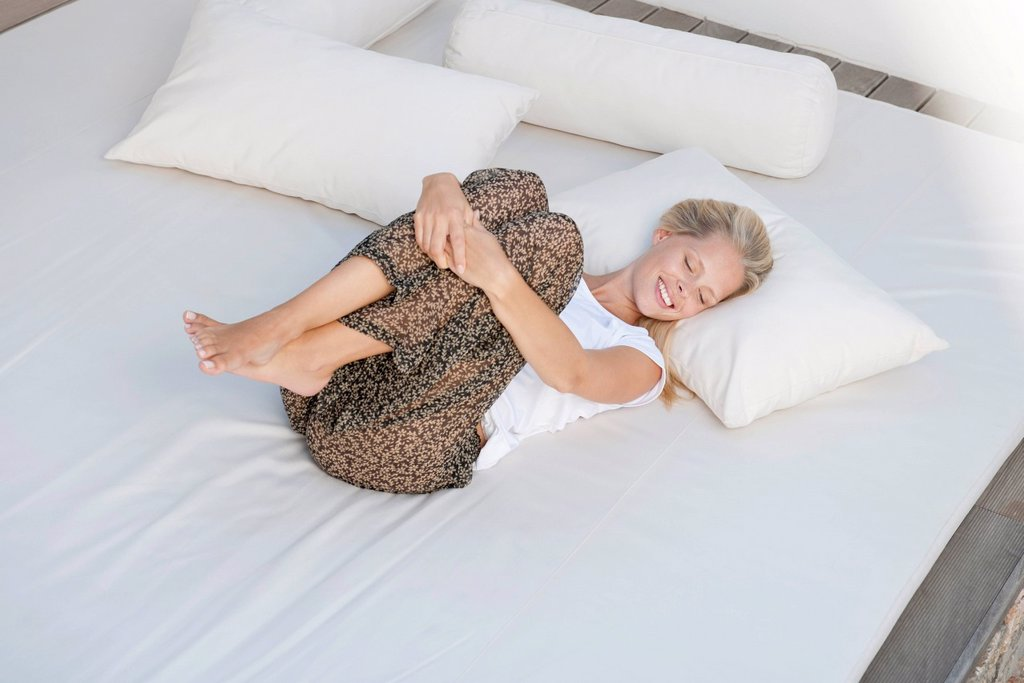 Young woman relaxing on bed in fetal position : Stock Photo