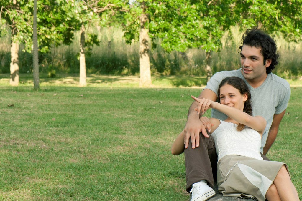 Young couple relaxing together in park : Stock Photo