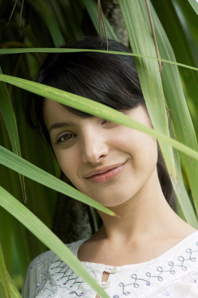 Young woman looking through foliage, portrait : Stock Photo