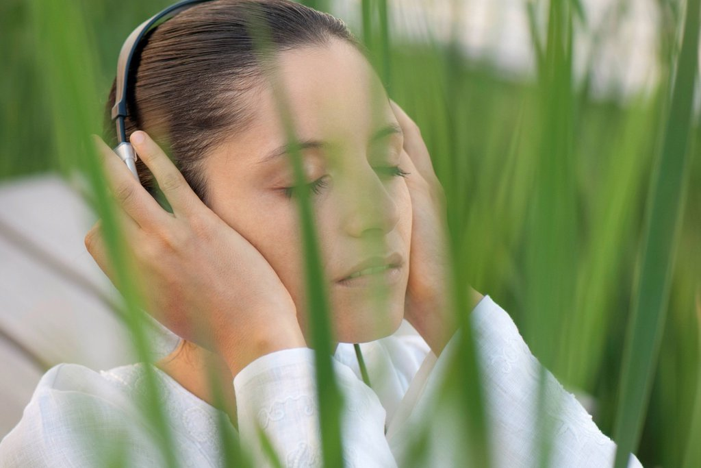Stock Photo: 1747R-18585 Young woman listening to headphones outdoors with eyes closed
