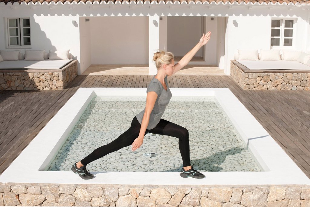 Young woman stretching legs in patio, side view : Stock Photo