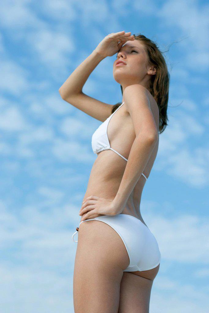 Young woman in bikini looking away, shading eyes : Stock Photo