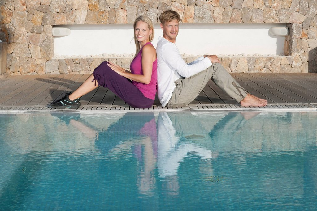 Stock Photo: 1747R-18624 Young couple sitting back to back at poolside, portrait