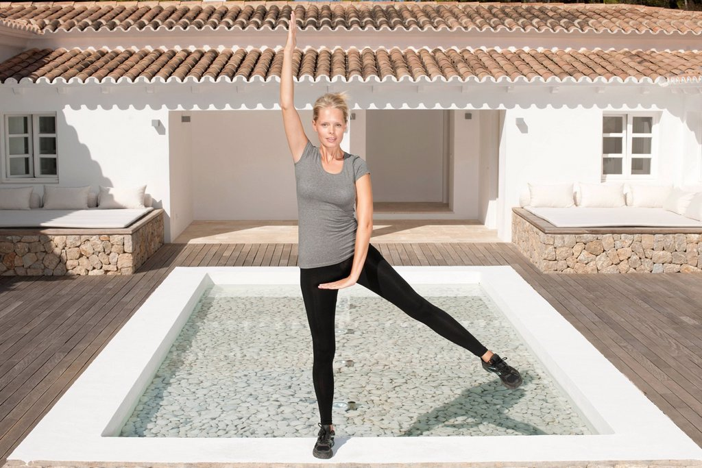 Young woman exercising in patio, standing on one leg : Stock Photo