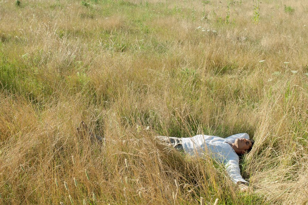 Mid_adult man relaxing in field with eyes closed : Stock Photo