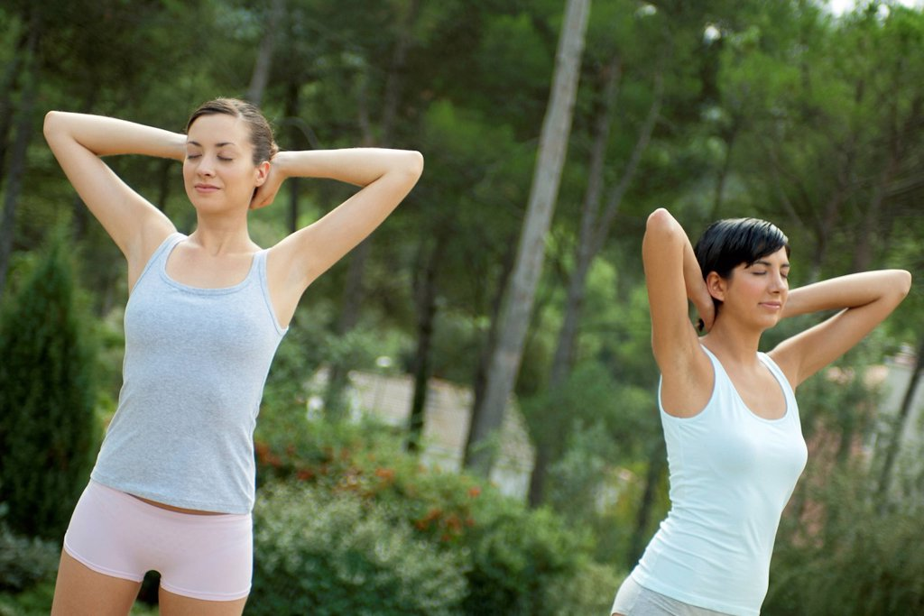 Young women exercising outdoors : Stock Photo