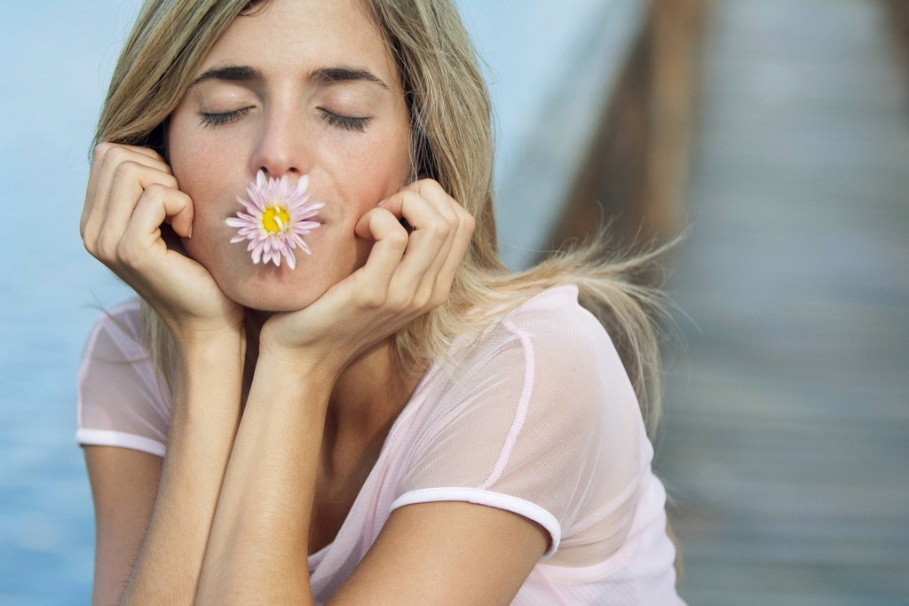Young woman holding flower in mouth with eyes closed : Stock Photo