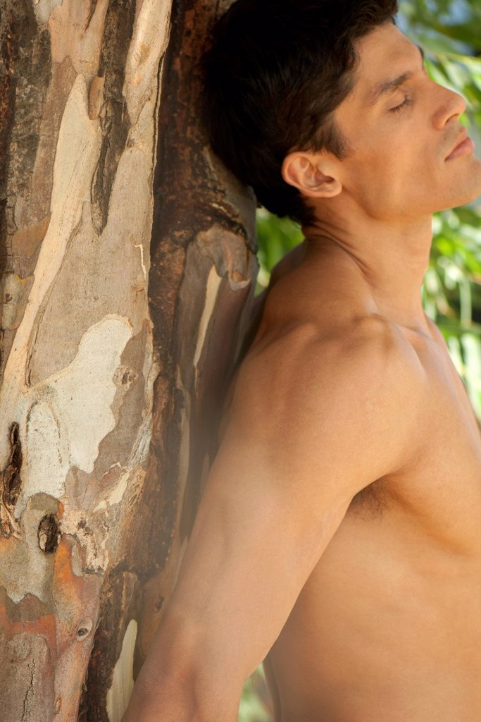 Stock Photo: 1747R-18651 Barechested man leaning against tree with eyes closed