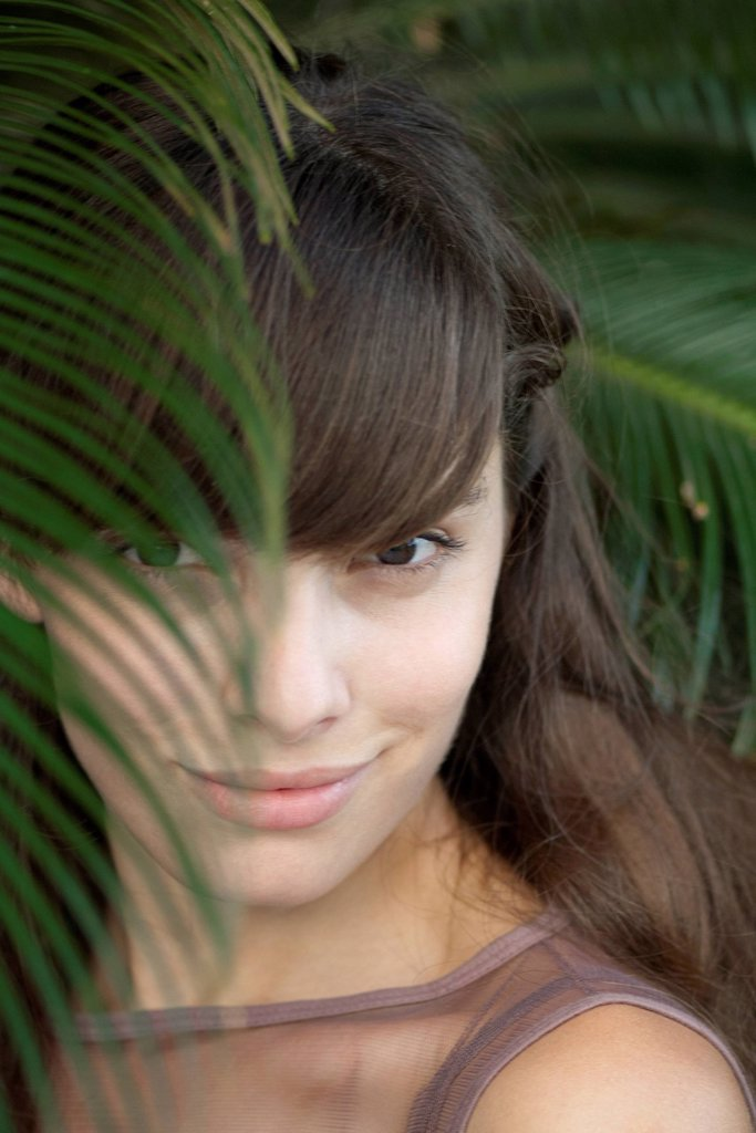 Stock Photo: 1747R-18652 Young woman behind palm frond, portrait