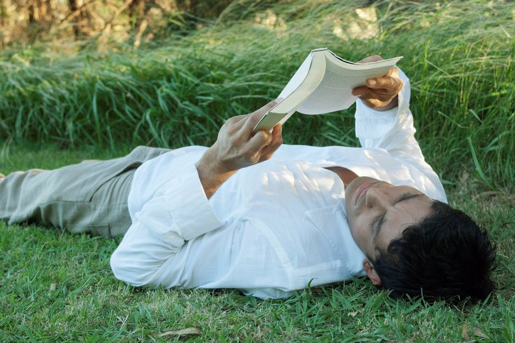 Stock Photo: 1747R-18685 Mid_adult man lying on grass reading book