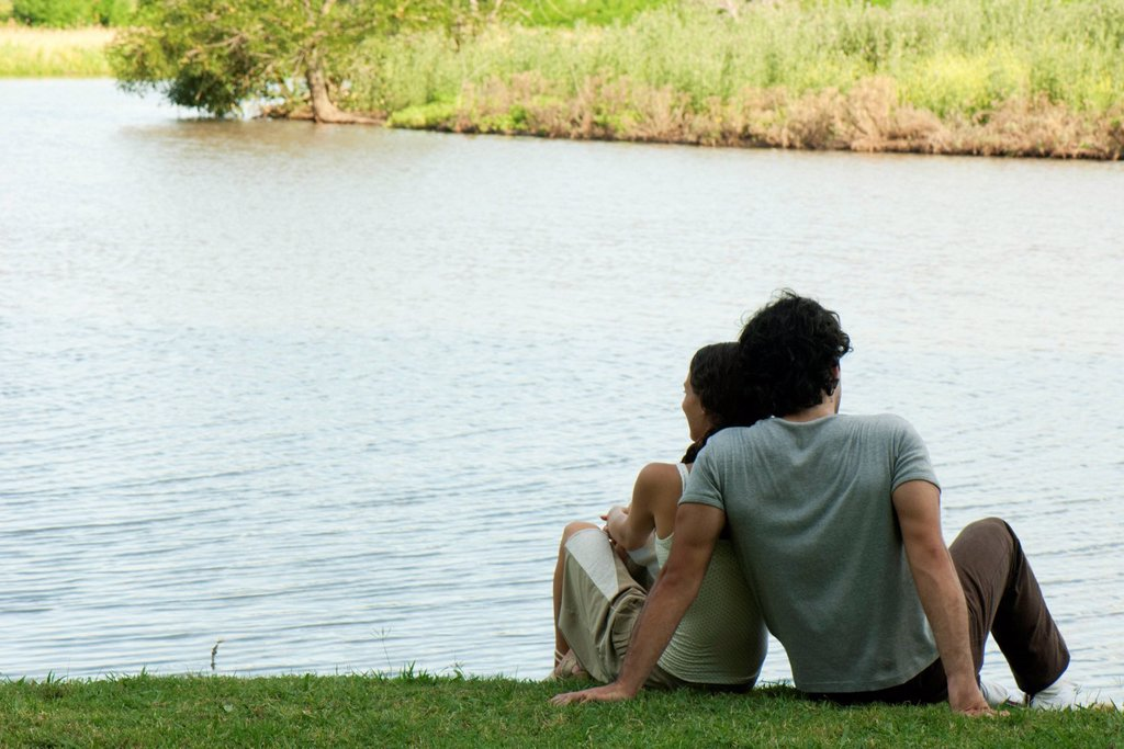 Couple sitting together by lake, rear view : Stock Photo