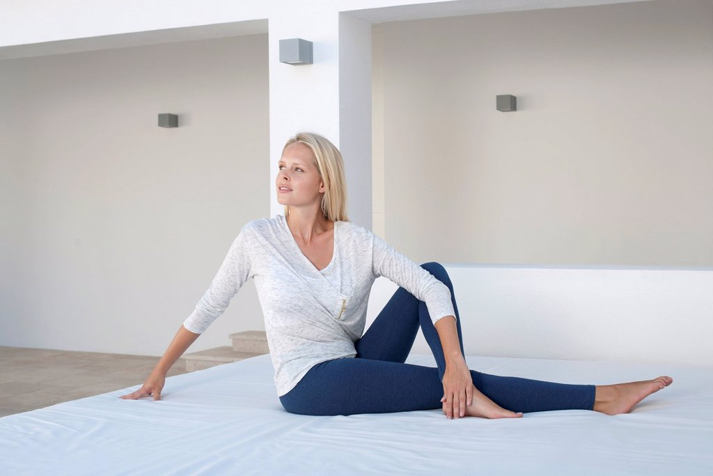 Stock Photo: 1747R-18698 Young woman doing spinal twist yoga pose on bed outdoors