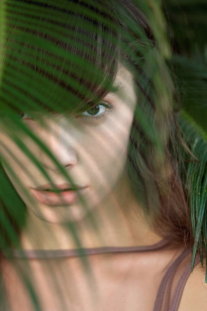 Stock Photo: 1747R-18702 Young woman behind palm frond, portrait