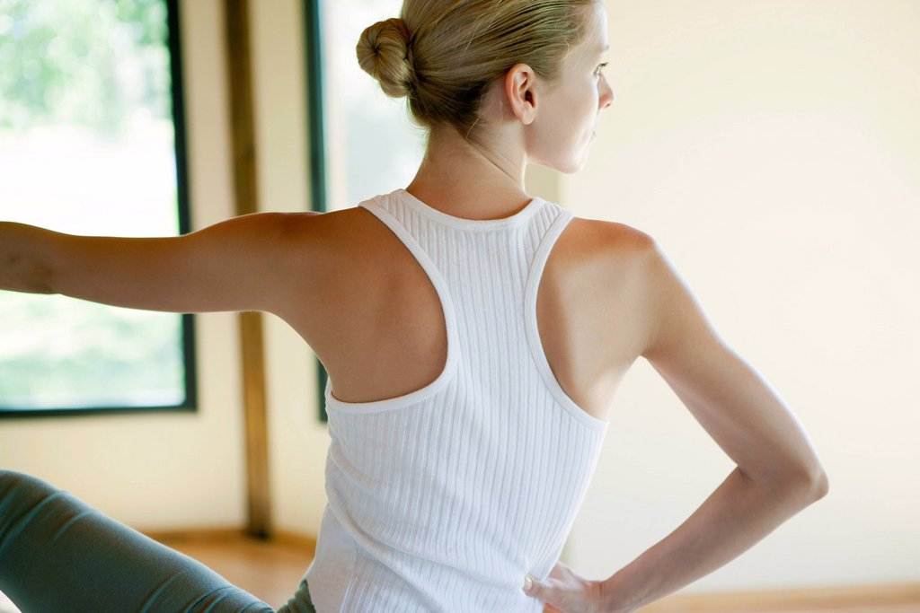 Stock Photo: 1747R-18709 Young woman doing seated spinal twist, rear view
