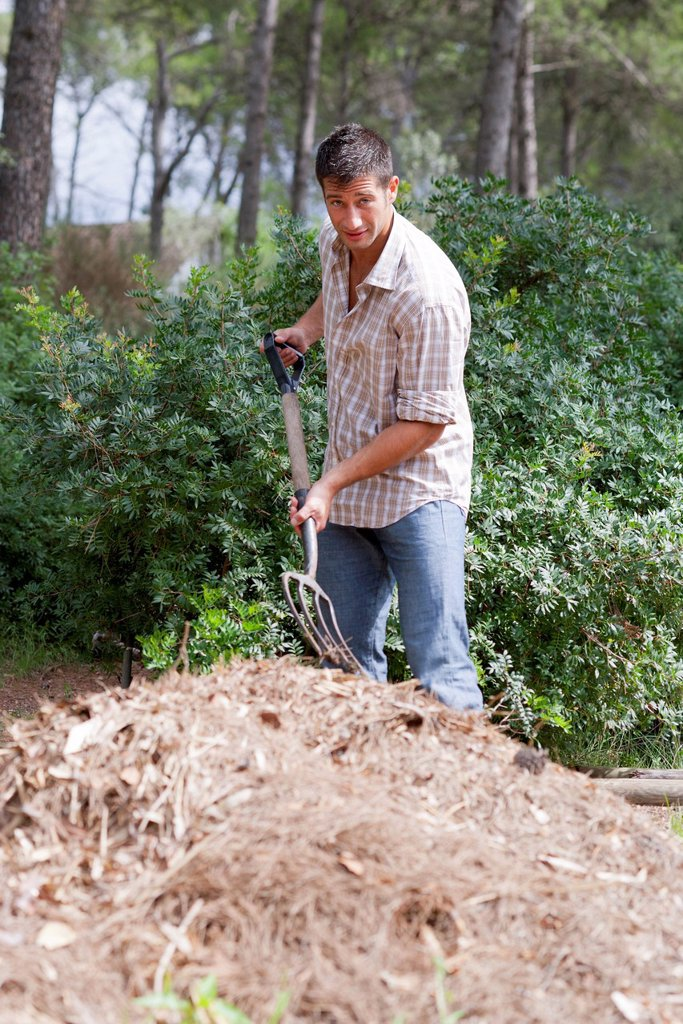 Stock Photo: 1747R-18712 Man standing by heap of straw, holding gardening fork