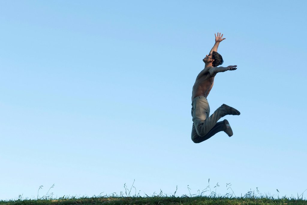Stock Photo: 1747R-18729 Barechested man jumping in air